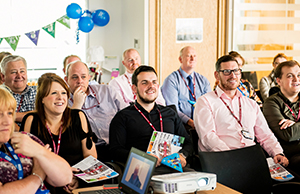 Photograph of NHS Informatics Merseyside colleagues listen to ten-year anniversary presentation