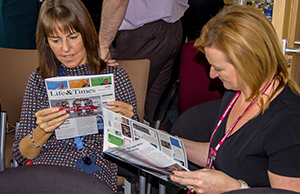 Photograph of colleagues reading the commemorative newsletter produced in celebration of the ten-year anniversary of NHS Informatics Merseyside