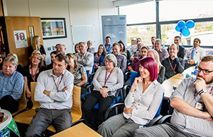 Photograph of colleagues listening to a presentation in celebration of the ten-year anniversary of NHS Informatics Merseyside